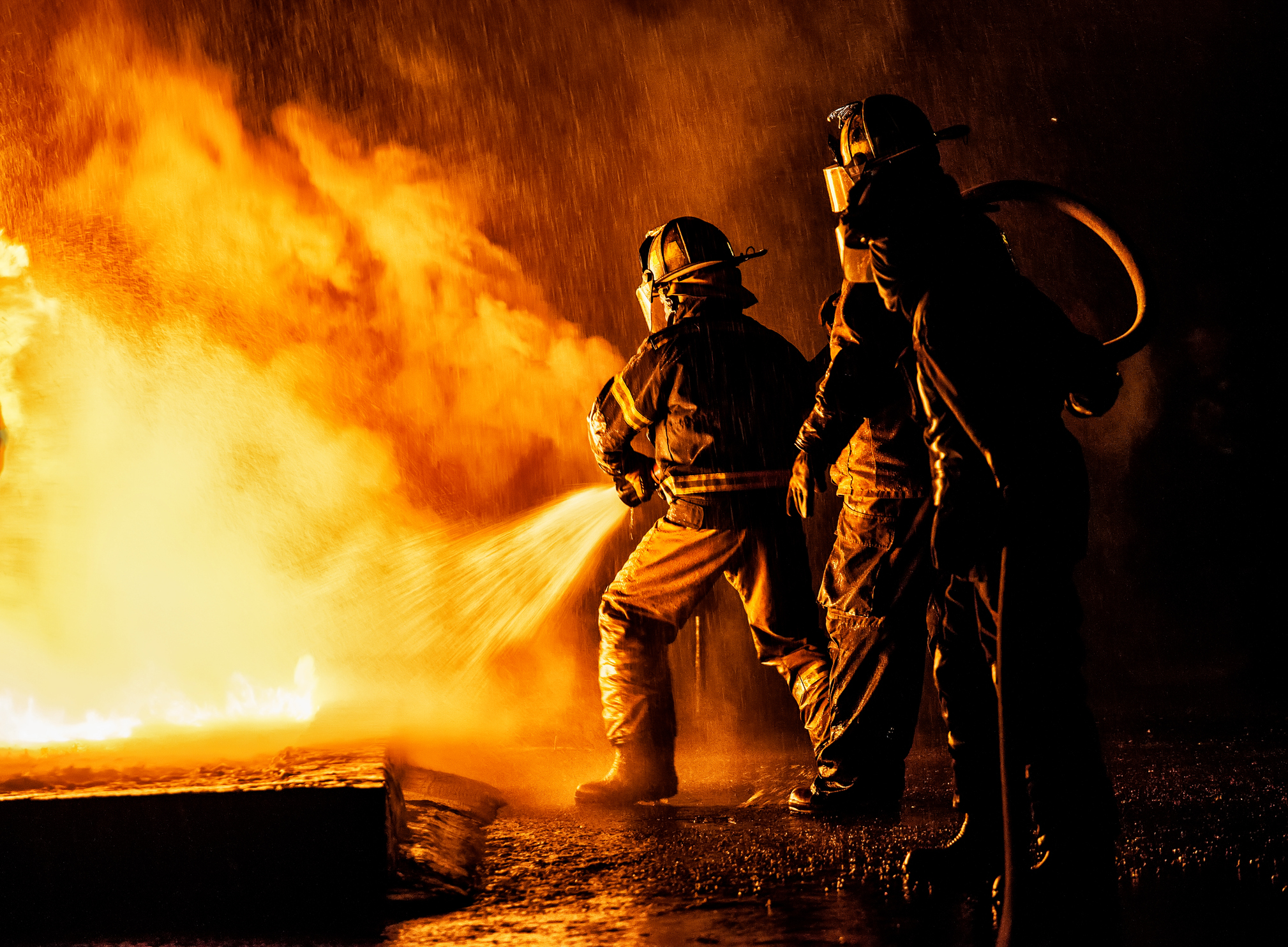 Two firefighters fighting a fire with a hose and water
